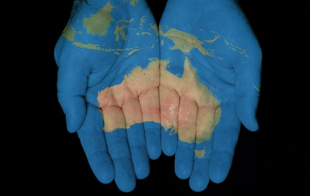 Map painted on hands showing concept of having Australia in our hands  photo