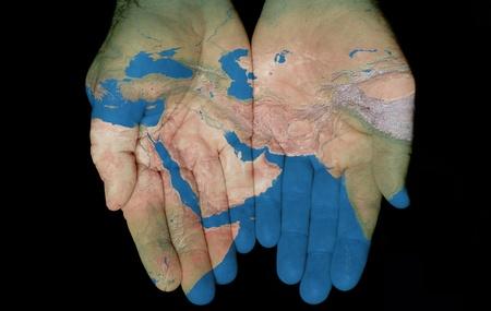 Map geschilderd op handen tonen begrip van het hebben van het Midden-Oosten in onze handen Stockfoto