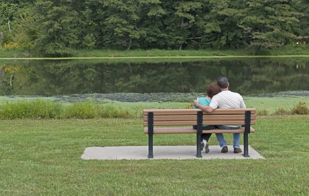 Couple In Love Sitting On A Park Bench in Spring photo