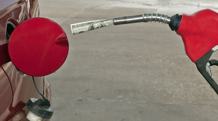 Gas Pump With A One Hundred  Dollar Bill -  Copy Space Below The Nozzle