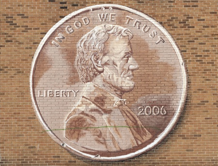 in god we trust: Lincoln Penny On A Brick Wall Stock Photo