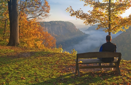 Man Sitting On A Bench Enjoying An Early Morning Sunrise Over A Foggy Geneseo River Valley At Letchworth State Park photo