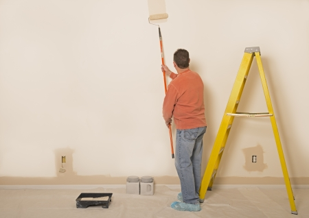 Man Painting A Wall With Room For Copy Space To The Left photo