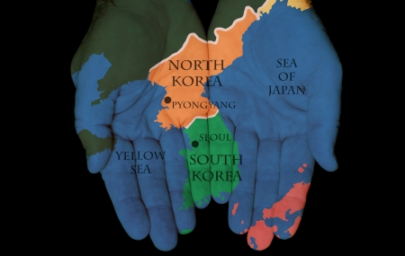 Map Painted On Hands Showing The Concept Of North Korea & South Korea In The Hands Of The People