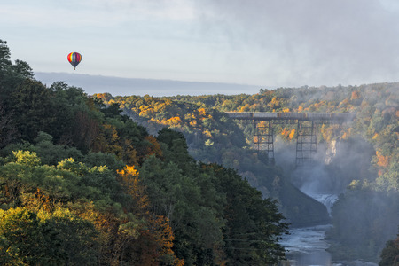 trestle: Sunrise From Inspiration Point At Letchworth State Park In New York With A Hot Air Balloon Flying Near The Railroad Trestle Stock Photo