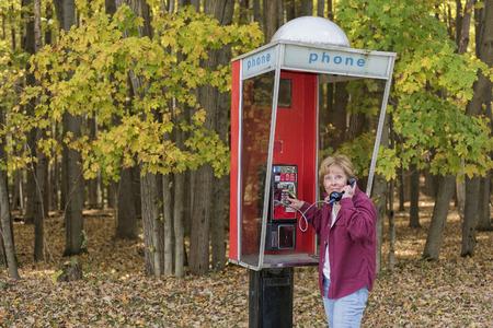 cabina telefonica: Mujer Adulta Usar el tel�fono al aire libre Cabina