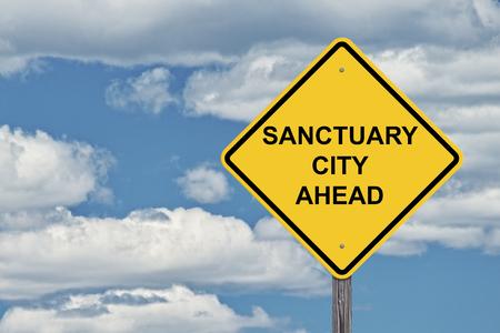 Caution Sign Blue Sky Background - Sanctuary City Ahead Stock Photo