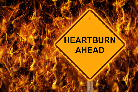 Heartburn Ahead Caution Sign With Flaming Background Stock Photo