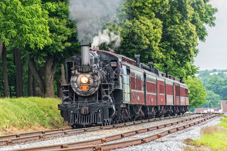 STRASBURG, PA - June 6, 2018: Strasburg Railroad Locomotive Canadian #89 pulls passenger cars through Lancaster County pastures. 에디토리얼