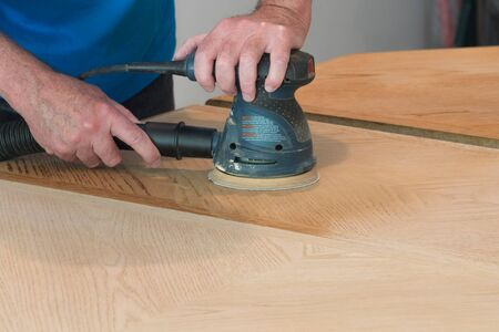 Closeup Of Man Sanding And Refinishing A TableTop
