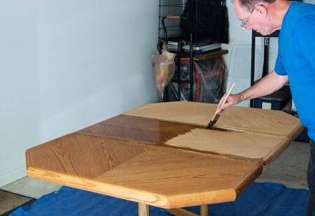 Man Staining And Refinishing A TableTop Stock fotó