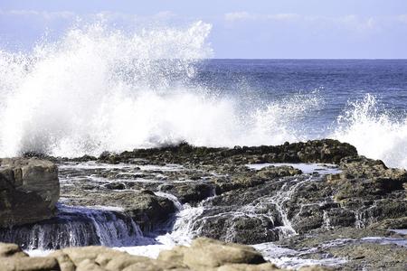 Onda che si infrange e acqua che scorre sulle rocce costiere, Uvongo, Sud Africa