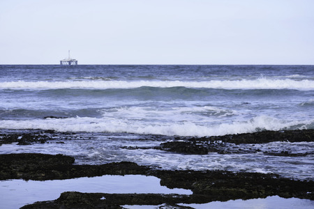 Rock Pools On Sea Shore With Ocean Horizon And Oil Drilling Platform In The Distance Stock Photo