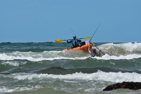 Fishermen With Ocean Kayak In The Waves, Mossel Bay, South Africa Archivio Fotografico