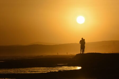 Young Couple On Vacation Beach Waiting For The Sunset, Mossel Bay, South Africa