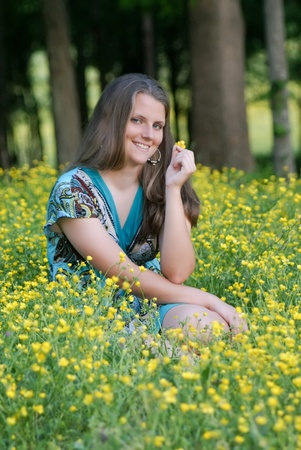 mischevious: Pretty girl sitting in a field of flowers smiling Stock Photo