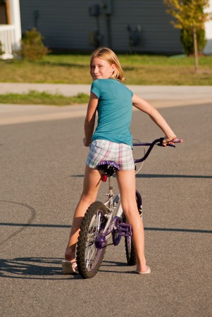 cousin: Girl on bicycle looking over her shoulder Stock Photo