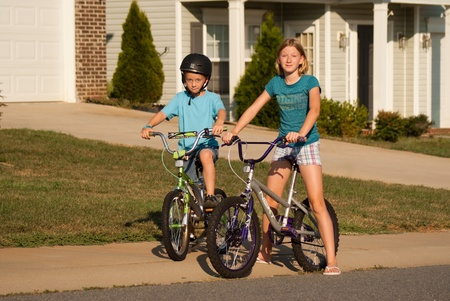 niños en bicicleta: Niño y niña en bicicleta con la mirada de sorpresa en sus rostros Foto de archivo