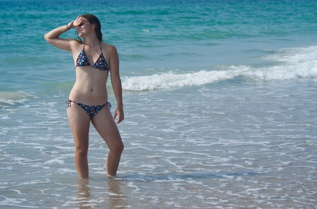 Woman at the beach in the water shielding her eyes from the sun photo