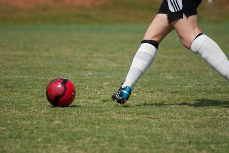 View of legs kicking soccer ball