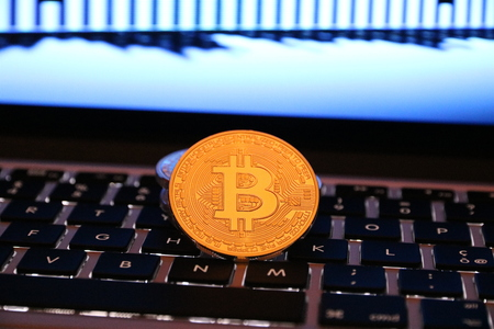 Golden Bitcoin currency over computer with background graphic