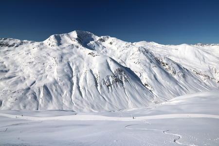 High mountain peak with snow and blue sky background