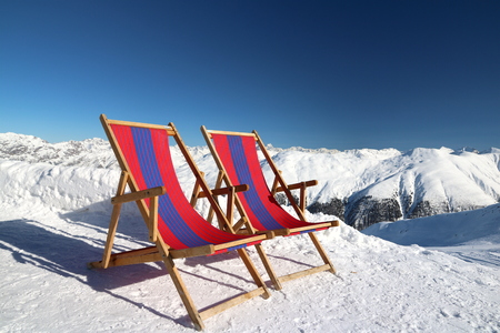 Colored deck chairs on the snow in the mountains