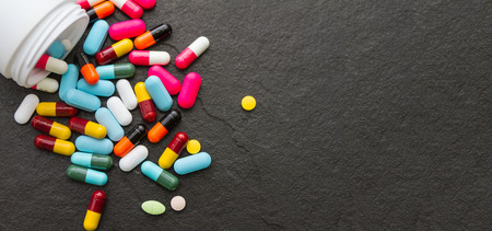 dragee: Many pills and tablets on black background for decorate and design project.