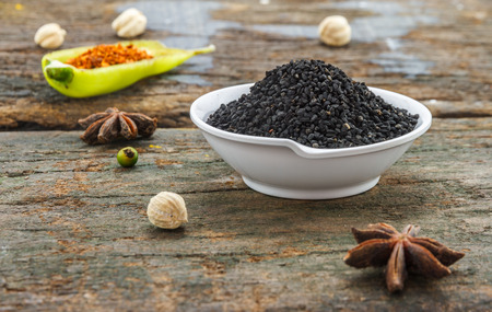 nigella seeds: The nigella seed on wood texture for design or decorate project.
