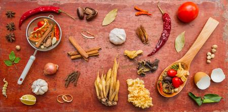 Mixed spices and herbs on red background for decorate design.