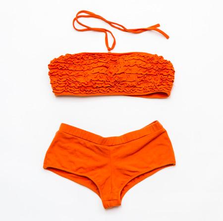 bikini top: Orange bikini swimsuit on white background for design.