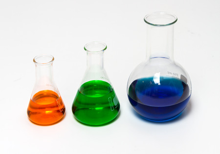 solubility: Group of laboratory flasks empty or filled with a clear liquid on white background. Stock Photo