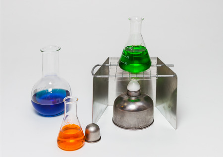 Group of laboratory flasks empty or filled with a clear liquid on white background. Stock Photo