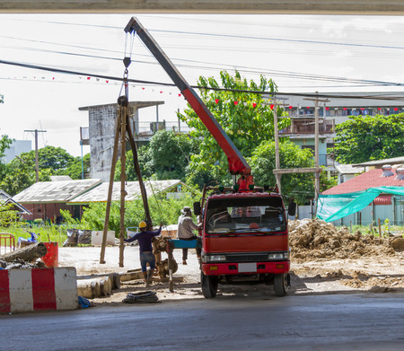 mobile crane: Construction worker in uniform and protective gear during hoisting works by mobile crane.