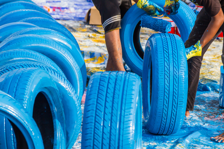 raceway: Worker painting  tire with roller at raceway on background. Stock Photo