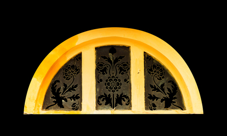 islamic wonderful: Golden light through carved window on black isolated background