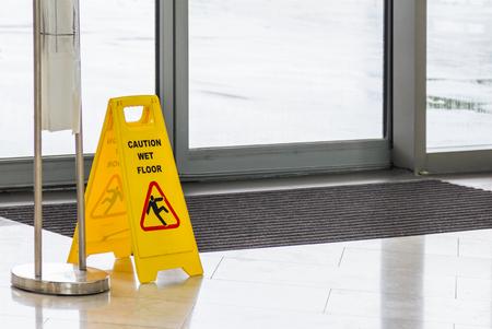 濡れ滑りやすい黄色注意は背景にサインオンします。