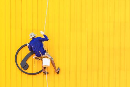 steeplejack: A worker climbing on a wall