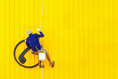 A man cleaning windows on a high rise building yellow color. Stock Photo