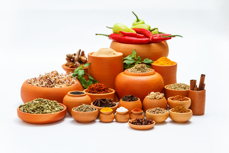 Spices and herbs on white background for decorate spices content,indian spices in terracotta pots, indian colourful spices,group of indian spices,Spices arranged in different size terracotta pots Stock Photo