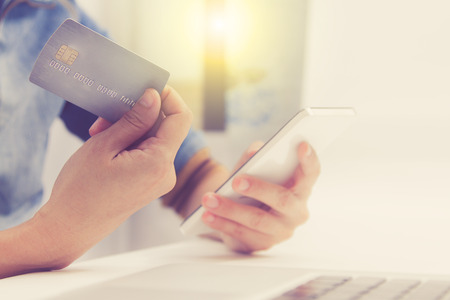 bankcard: Online payment, hands holding a credit card and using smart phone for online shopping,credit card content,credit card background.