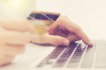 bankcard: Hands holding credit card and using laptop. Online shopping,credit card content,credit card background.