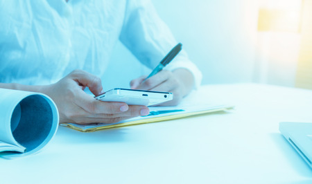 businees: Businesswoman holding mobile phone and looking data on monitor about meeting subject for dicuss at meeting room, businees content, business background.(Cool tone)