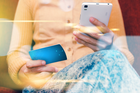 bankcard: Online payment, hands holding a credit card and using smart phone for online shopping,credit card content,credit card background and selective focus.