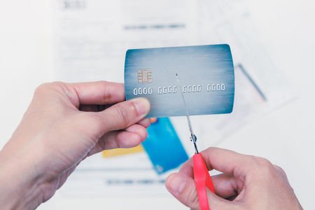 indebted: Hands cutting a credit card with scissors,woman is cutting credit card or bank card with scissors over contract and other credit cards Stock Photo
