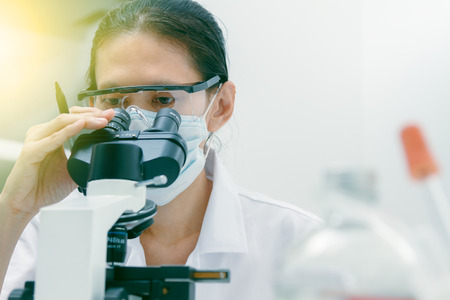 Close up of female scientist looking to microscope in clinical laboratory chemical formula and dna molecule structure,science concept,science people and selective focus.