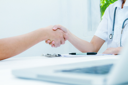 professionalism: Doctor at the clinic giving an handshake to his patient, healthcare and professionalism concept,Doctor shakes hands with a patient isolated on white background,medical background,medical concept and selective focus.