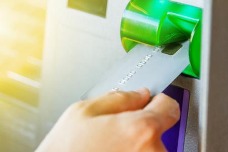 automatic transaction machine: Dé la inserción de tarjeta de cajero automático en la máquina del banco para retirar dinero, la mano de la mujer con tarjeta de crédito, utilizando un cajero automático, fondo finace, conocimiento de los negocios y el enfoque selectivo. Foto de archivo