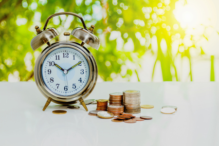 monete antiche: Alarm clock and money,coins stack and alarm clock on background,finance concept,business background and selective focus. Archivio Fotografico