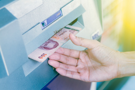 automatic transaction machine: Cajero automático que retira el dinero, primer de la persona que retira el dinero de la máquina de la atmósfera, concepto de las finanzas, fondo del negocio y foco selectivo.